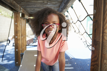 Young black girl in school playground, looking to camera