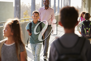 Male teacher and pupils walking on busy school campus