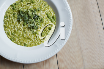 Overhead Shot Of Dish Of Pea And Mint Risotto On Wooden Restaurant Table