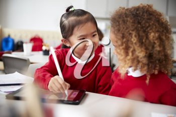 Close up of two kindergarten schoolgirls wearing school uniforms, sitting at a desk in a classroom using a tablet computer and stylus, looking at each other smiling
