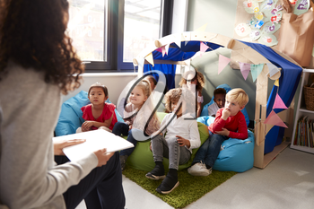 Female infant school teacher sitting on a chair reading a book to a group of children sitting on bean bags in a comfortable corner of the classroom, elevated view, close up