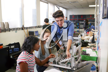 Teacher With Two Female College Students Building Machine In Science Robotics Or Engineering Class