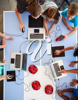 Overhead View Of Students In After School Computer Coding Class Learning To Program Robot Vehicle