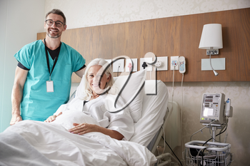 Portrait Of Surgeon Visiting Mature Female Patient In Hospital Bed