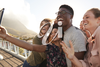 Smiling Young Friends Posing For Selfie On Outdoor Footbridge Together