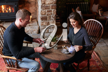 Couple Sitting At Table Drinking Tea In Traditional English Holiday Hotel