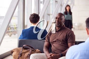 Mature Businessman Sitting And Waiting In Airport Departure Lounge