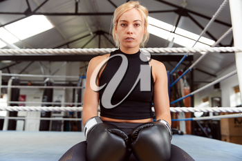 Portrait Of Female Boxer With Gum Shield In Gym Wearing Boxing Gloves Sitting On Boxing Ring