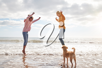 Mother And Daughter With Dog Jumping Over Waves On Autumn Beach Vacation