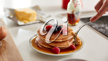 Woman Eating Freshly Made Pancakes Or Crepes With Syrup And Berries On Table For Pancake Day
