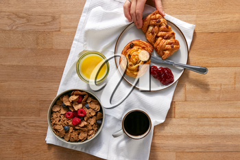 Overhead Flat Lay Of Woman Eating At Table Laid For Breakfast With Cereal Croissant And Pastries
