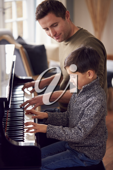 Young Boy Learning To Play Piano Having Lesson From Male Teacher