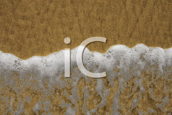 Royalty Free Photo of a Close-up of a Frothy Ocean Wave on a Sandy Beach