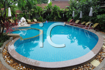 Whimsically curved pool with crystal clear water surrounded by palm trees, statues and sun loungers