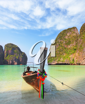 Scenic green islands of Thailand coast. Emerald sea and fine white sand. In sand moored tourist boat, decorated with red silk scarf and a flower wreath