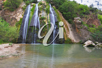 The original three-jet Falls on the border of Israel. Three parallel streams of water running down the steep slope and fall in oval pool