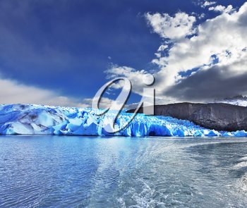Journey to the End of the World. Chilean Patagonia in the sunlight. Blue Ice Glacier Gray is reflected in the lake