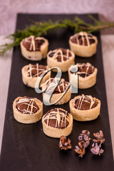 Professional baking. Magnificent portioned tartlet cakes  with chocolate filling. Background black