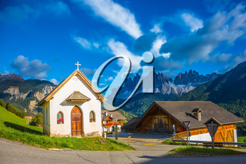 Magnificent serrated cliffs and small chapel in the Dolomites illuminate the summer sunset. The concept of eco-tourism in Tirol
