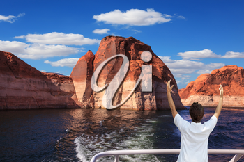 The elderly woman in white aft boats is delighted with the nature. The artificial lake Powell on the river Colorado, USA. The lake it is surrounded with picturesque coast from orange sandstone