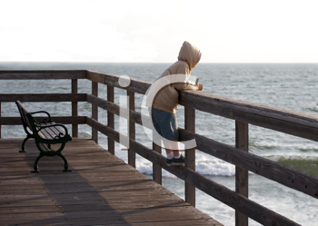 Royalty Free Photo of a Child Alone on a Boardwalk Railing