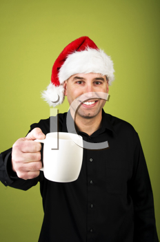 Royalty Free Photo of a Man in a Santa Hat Holding Out a Cup