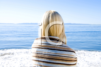 Royalty Free Photo of a Woman Wrapped in a Towel Looking at the Ocean