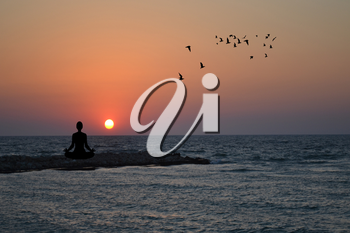 Silhouette of woman practising yoga and meditating on sunrise