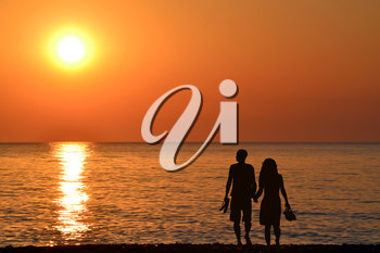 Back view of a couple silhouette walking together on the beach at sunrise in summer