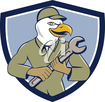 Illustration of a american bald eagle mechanic holding spanner looking to the side viewed from front set inside shield crest on isolated background done in cartoon style.