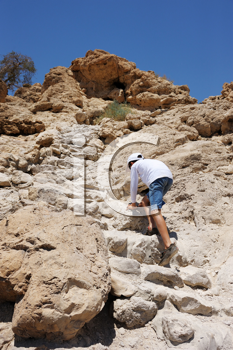 Royalty Free Photo of a Boy Climbing Stones to the Top of a Mountain