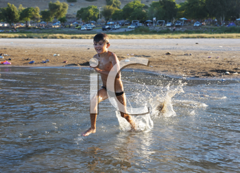 Royalty Free Photo of a Boy Running in Water