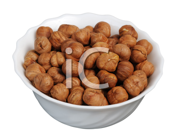Hazelnuts on a white plate on a white background, isolated.
