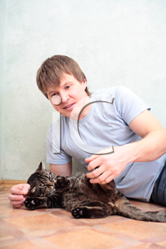 relaxed man lying on the floor with cat against wall