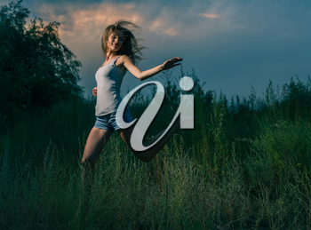 Happy girl jumping in grass. Blurre motion image
