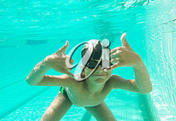 Portrait of a cute little boy swimming underwater and gesturing - OK sign and a lot of copyspace