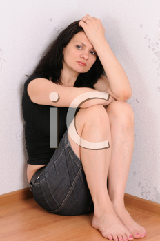 Royalty Free Photo of a Woman Sitting in a Corner
