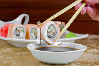 hand holding sushi with chopsticks at table