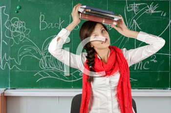Young student girl with her books at blackboard background