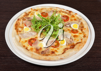 meat pizza with chicken, rukkola and eggs at the table