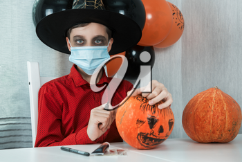 Teen boy in costume preparing for the Halloween celebration drawing a pumpkin. Halloween carnival with new reality with pandemic concept. Children wearing face masks to protect against COVID-19.
