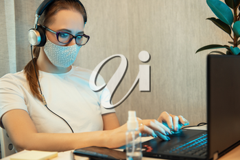 Coronavirus concept. Woman in quarantine for coronavirus covid-19 working from home. Protective mask and Sanitizer spray on the working place