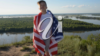 Blonde boy waving national USA flag outdoors over blue sky at the river bank.
