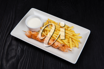 Grilled salmon fish shashlik with fried potatoes and sauce on white plate on black wooden background