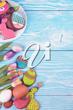 Tulips and gingerbread cookies on white and blue wooden background for Easter.