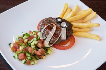 Funny meat cutlet face with french fries as hair and cutted vegetables for children menu