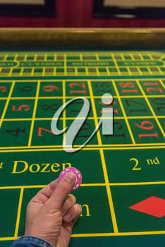 Casino, gambling and entertainment concept - male hand with stack of poker chips on a green table background