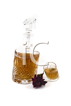 Crystal decanter with jigger and flower for alcoholic beverage over white