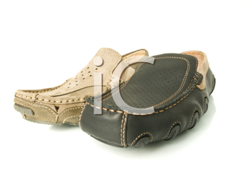 Modern beige and black mens moccasins over white background (wide angle shot)