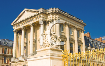 Statue and palace facade with columns in Versailles, France